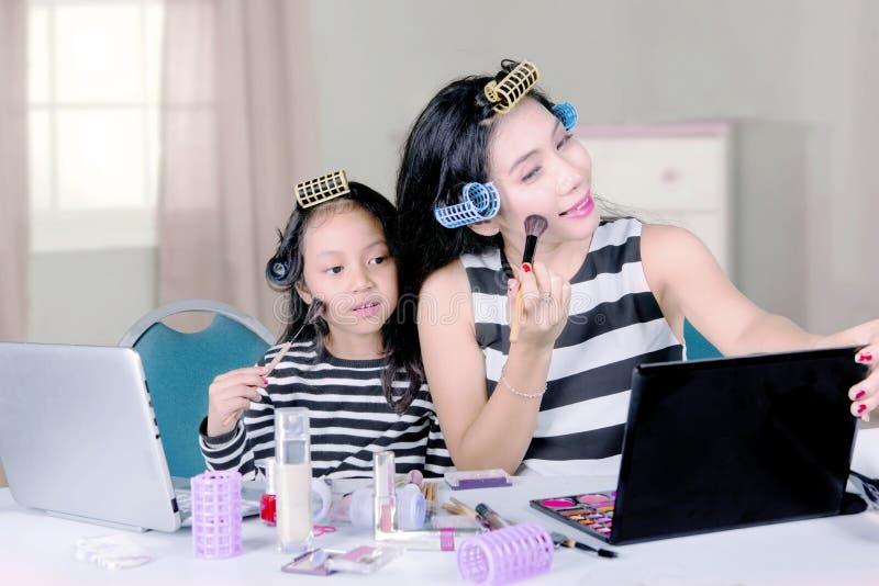Vrouw en kind die make-up in de slaapkamer doen royalty-vrije stock fotografie