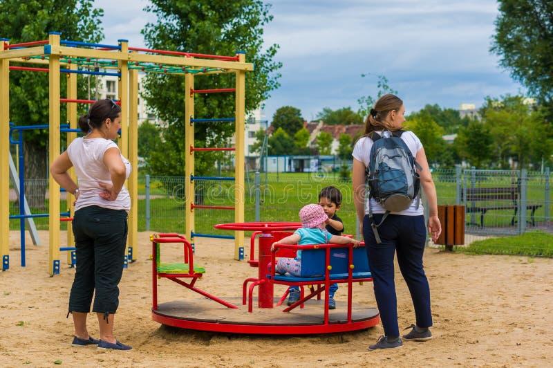 Vrouw en kinderen door rotonde stock afbeeldingen