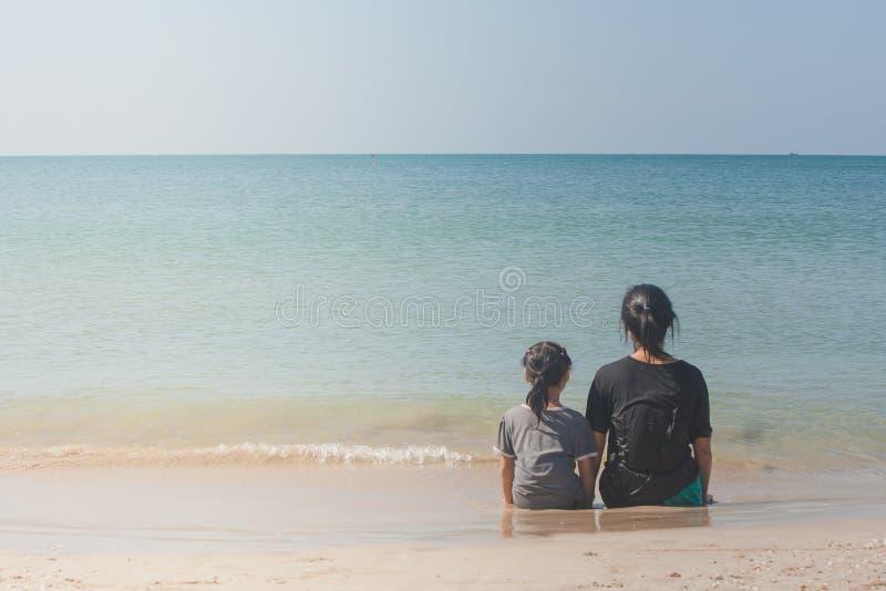 Vrouw en kinderen zitten rijtjes op zandstrand en het kijken aan zeegezicht royalty-vrije stock afbeelding