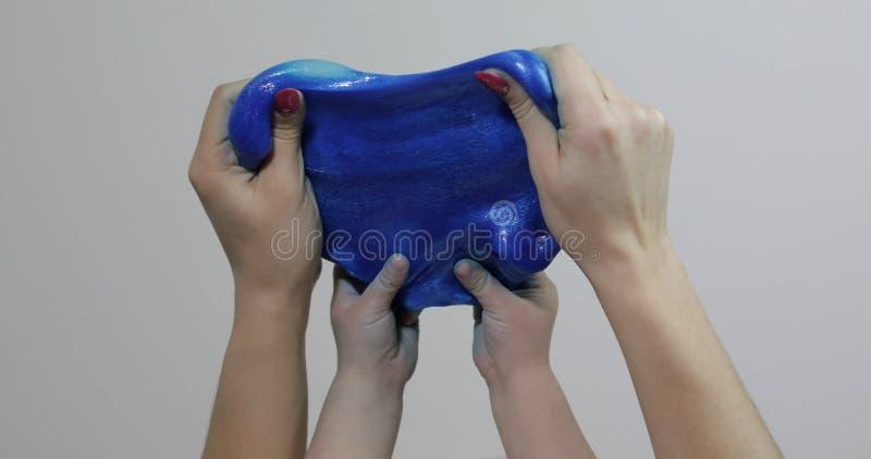 Vrouw en kindhanden die tevredenstellend de blauwe substantie van slijmgooey spelen Antistress royalty-vrije stock afbeeldingen