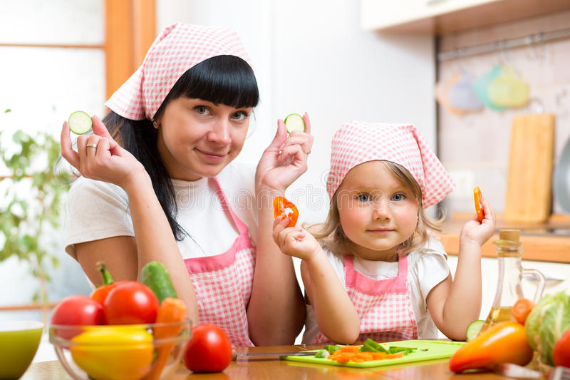 Vrouw en kindmeisje die groenten in de keuken voorbereiden stock fotografie