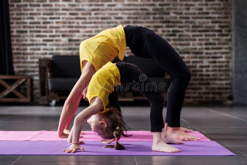 Vrouw en kindmeisje het praktizeren de yoga die samen thuis, zich in brug bevinden stelt royalty-vrije stock fotografie