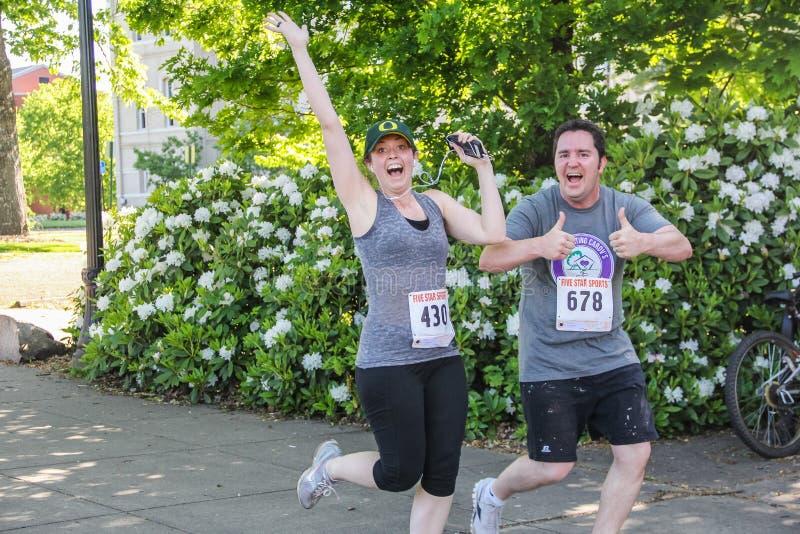 Vrouw en man de agenten geven gelukkige tekens tijdens 5K looppas stock foto