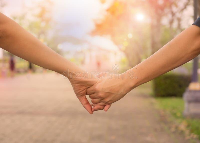 Vrouw en man de handen van de holdingsschok, stock afbeelding