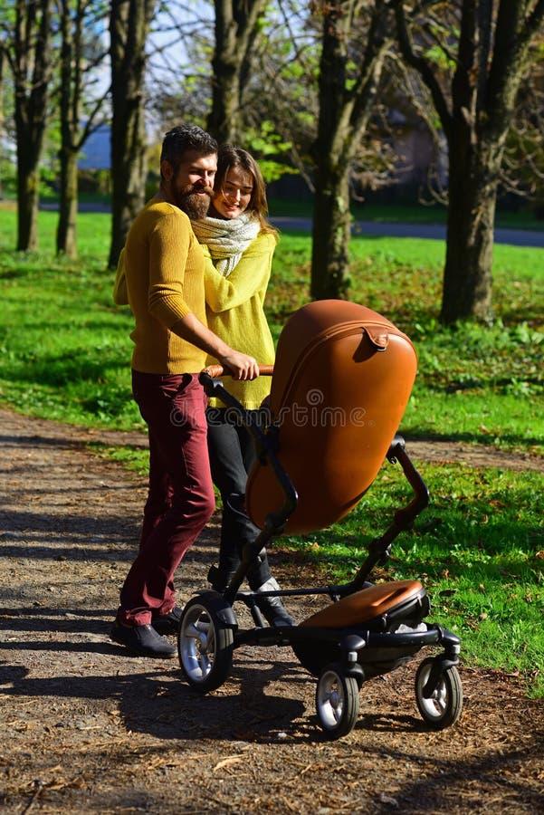Vrouw en man de ouder duwt babywandelwagen terwijl het lopen door de herfstpark, familieband Gelukkige familieband Genoegen van stock afbeeldingen