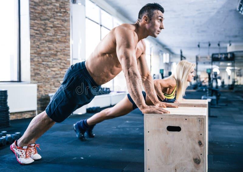 Vrouw en man die duw UPS doen bij gymnastiek stock fotografie