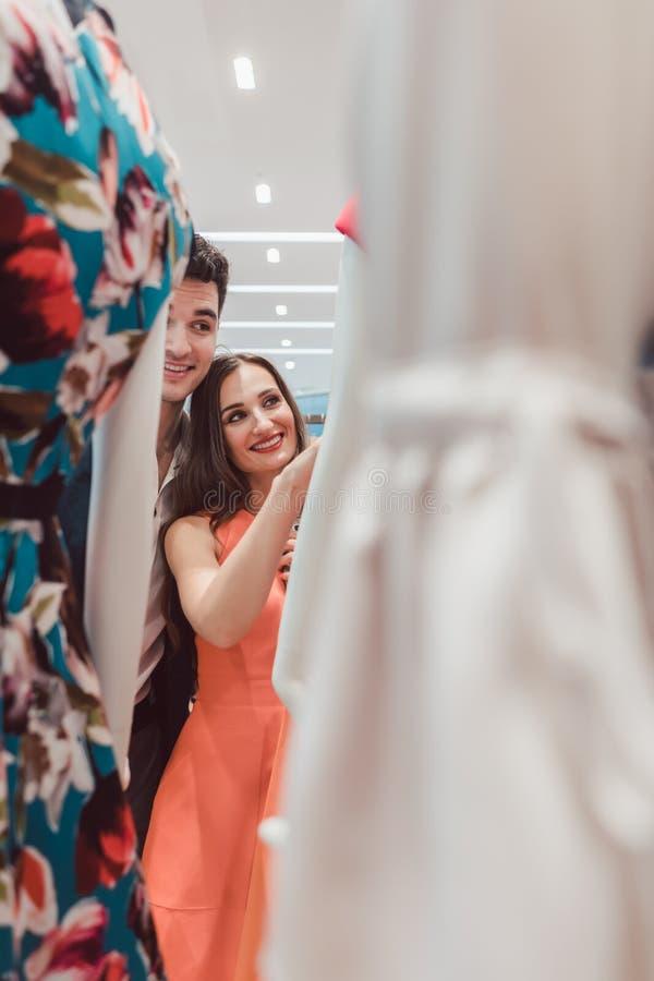 Vrouw en man die kleding op een ledenpop in manieropslag bekijken royalty-vrije stock fotografie