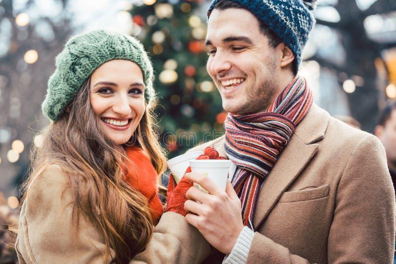 Vrouw en man die overwogen wijn op Kerstmismarkt drinken stock foto