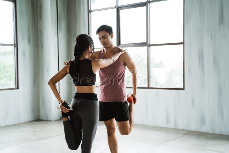 Vrouw en man die vóór training opwarmen stock foto