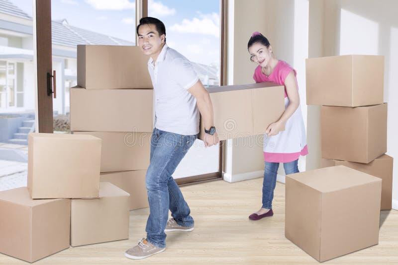 Vrouw en man dragende doos thuis royalty-vrije stock fotografie