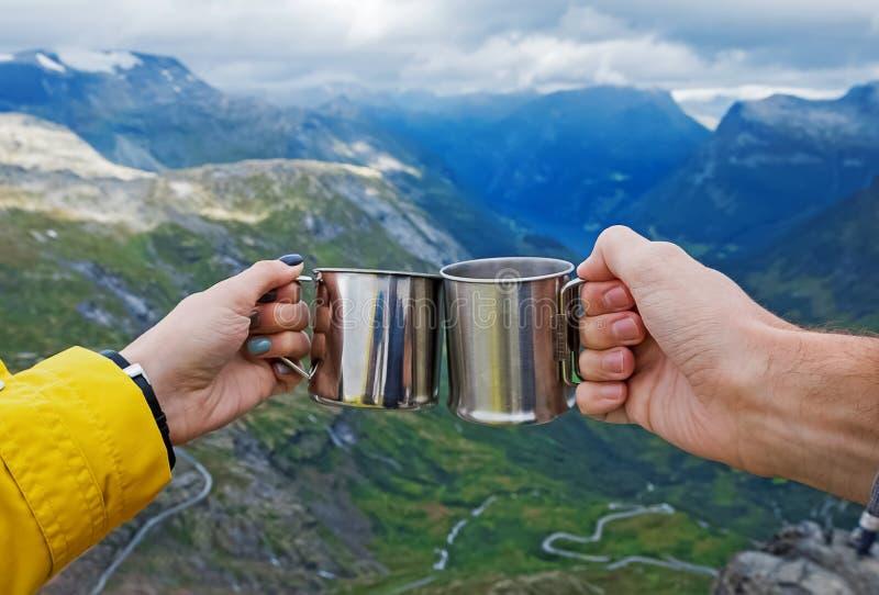 Vrouw en man hand die het kamperen mokken met hete thee samenhouden stock fotografie