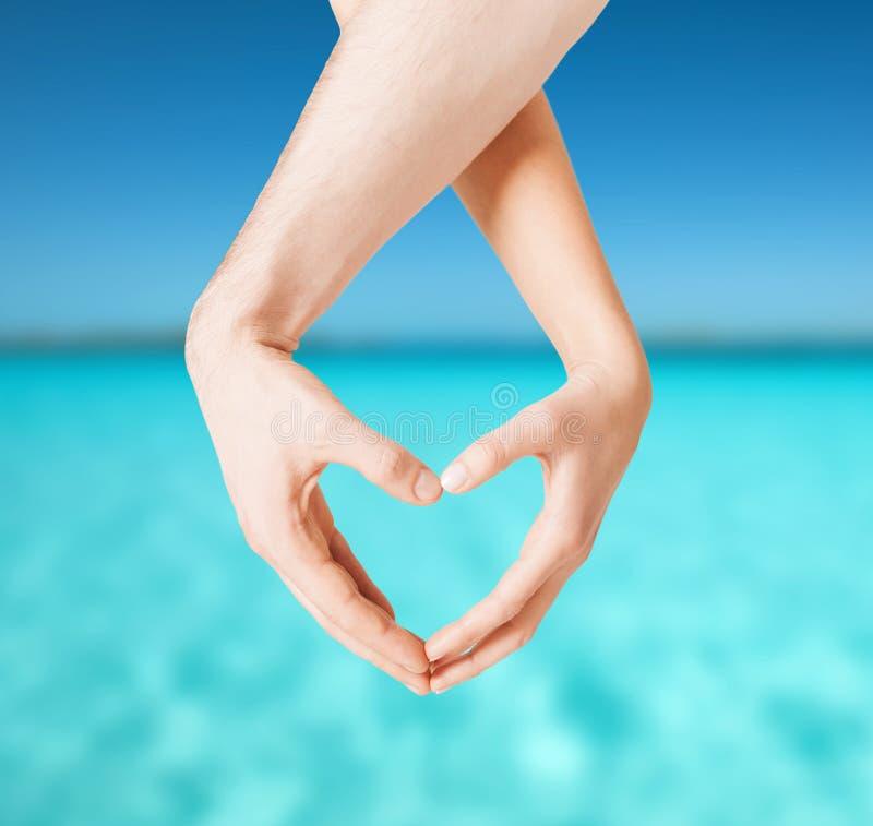 Vrouw en man handen die hartvorm tonen stock fotografie