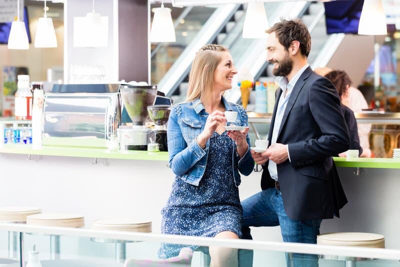 Vrouw en man het drinken koffie in koffie royalty-vrije stock afbeelding