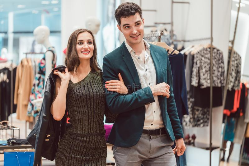 Vrouw en man het winkelen kleren in manieropslag royalty-vrije stock afbeeldingen