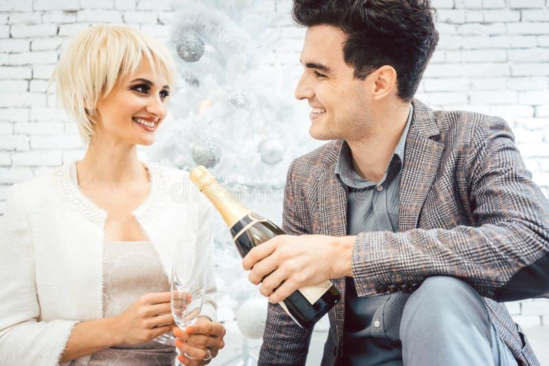 Vrouw en man onder witte Kerstboom met mousserende wijn royalty-vrije stock afbeelding