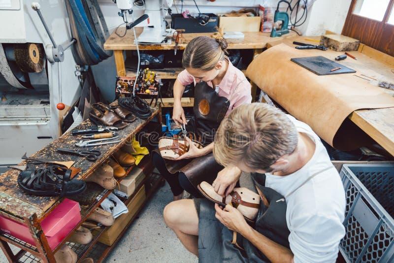Vrouw en man schoenenwerker werken samen royalty-vrije stock afbeeldingen