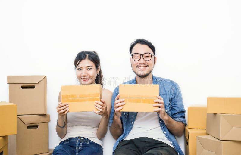 Vrouw en man wat hun handen die doos houden die thuis concept, online marketing verpakking en levering werken stock foto's