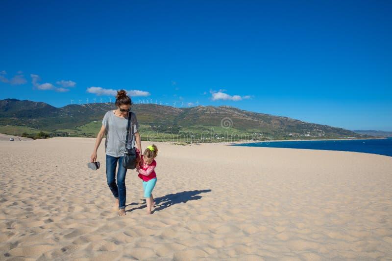 Vrouw en meisje die op zand van Valdevaqueros-Strand in Cadiz lopen royalty-vrije stock foto's