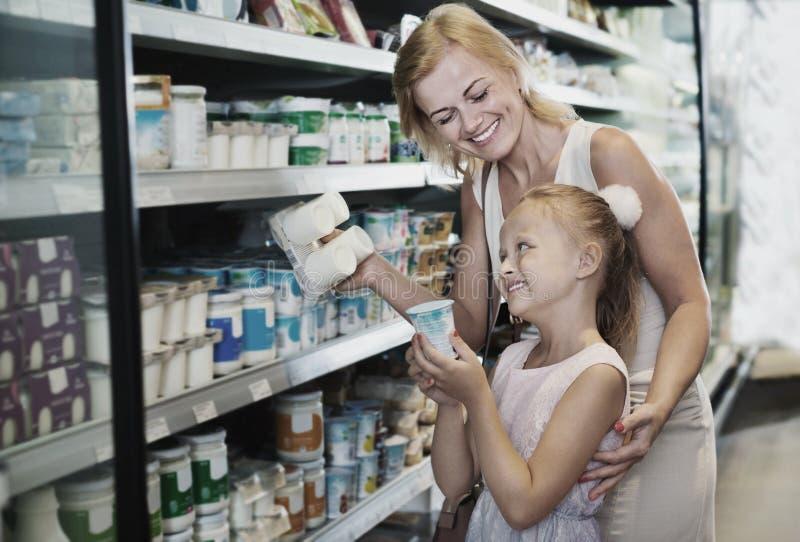 Vrouw en meisje die verse zuivelproducten in gekoelde sekte plukken royalty-vrije stock afbeeldingen
