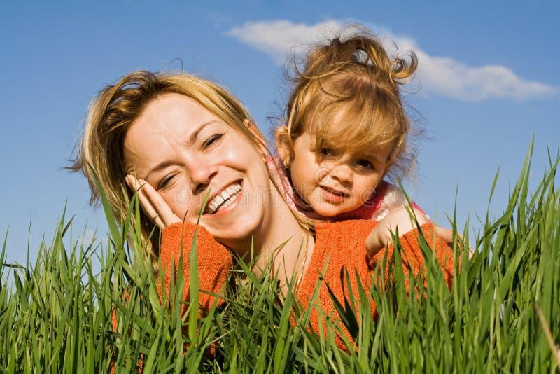 Vrouw en meisje in het gras stock afbeeldingen