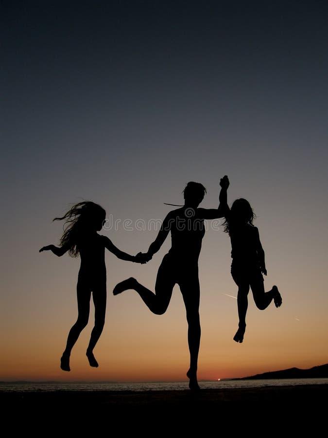 Vrouw en meisjes die in zonsondergang springen royalty-vrije stock afbeelding