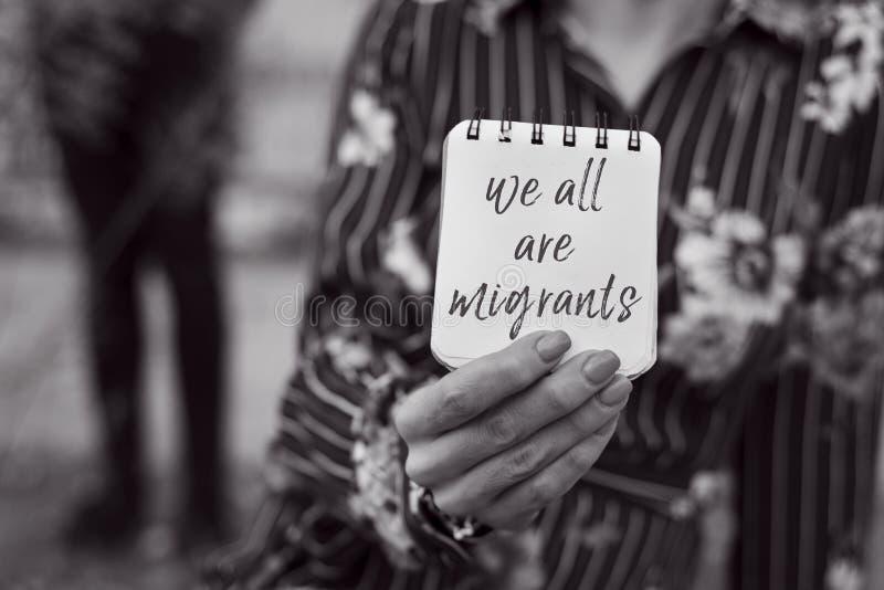 Vrouw en nota met de tekst zijn wij allen migranten stock foto