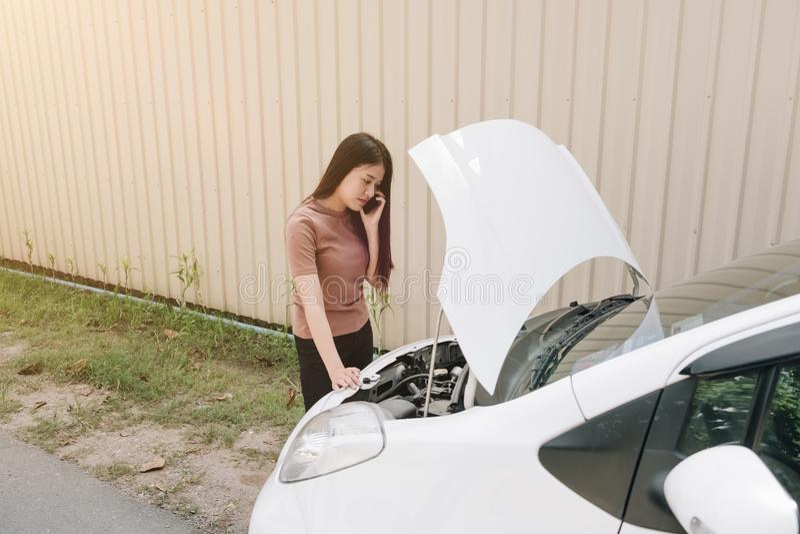 Vrouw en opgesplitste auto op straat, Meisje die mobiele telefoonwhi gebruiken stock afbeelding
