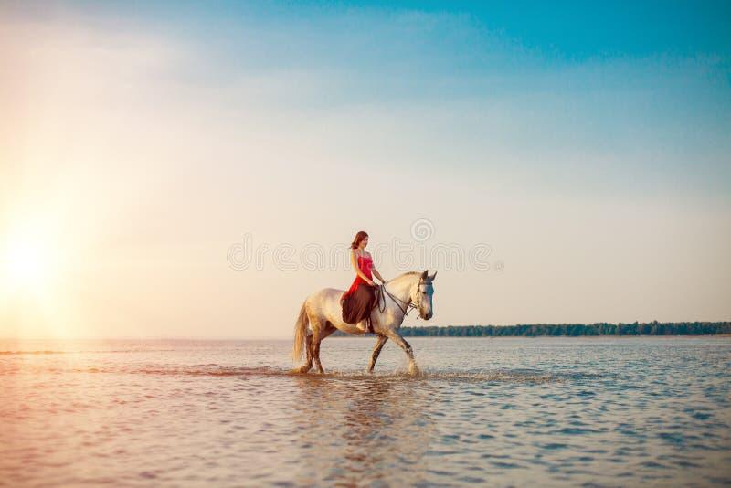 Vrouw en paard op de achtergrond van hemel en water Meisje modelo royalty-vrije stock foto