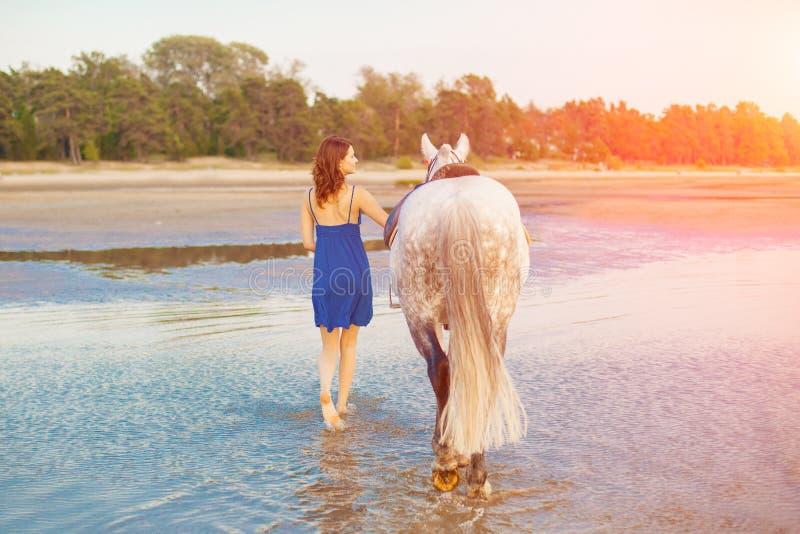 Vrouw en paard op de achtergrond van hemel en water Meisje modelo stock foto