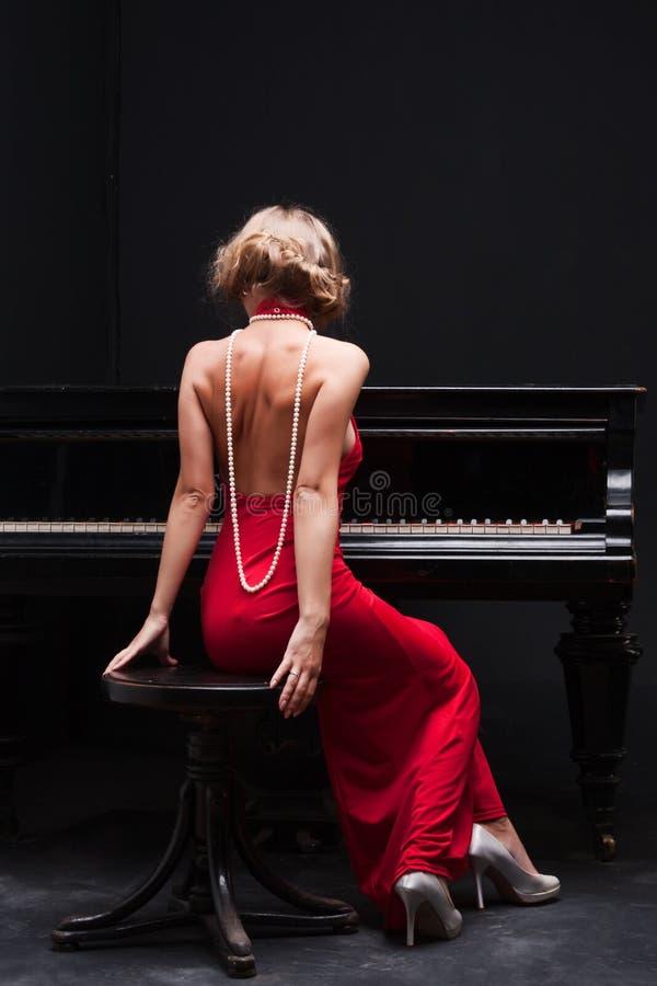 Vrouw en piano stock afbeeldingen