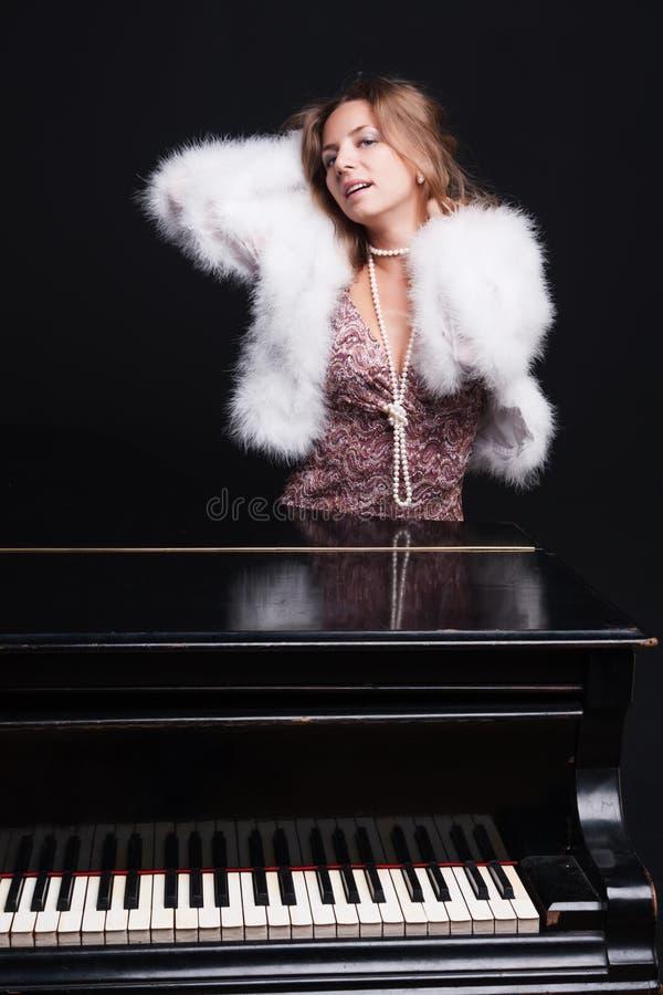 Vrouw en piano stock fotografie