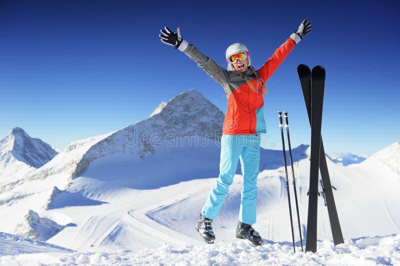 Vrouw in en Skitoevlucht die springen glimlachen royalty-vrije stock afbeelding