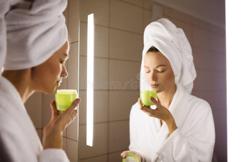 Vrouw en spiegel in badkamers Holdingsroom stock foto