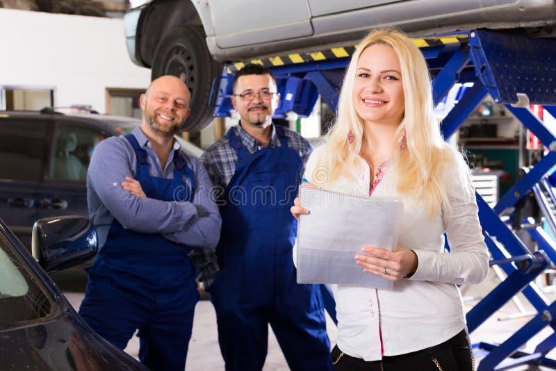 Vrouw en twee autowerktuigkundigen stock foto's