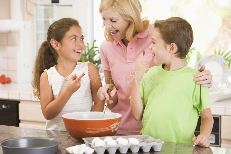 Vrouw en twee kinderen in keukenbaksel royalty-vrije stock afbeeldingen