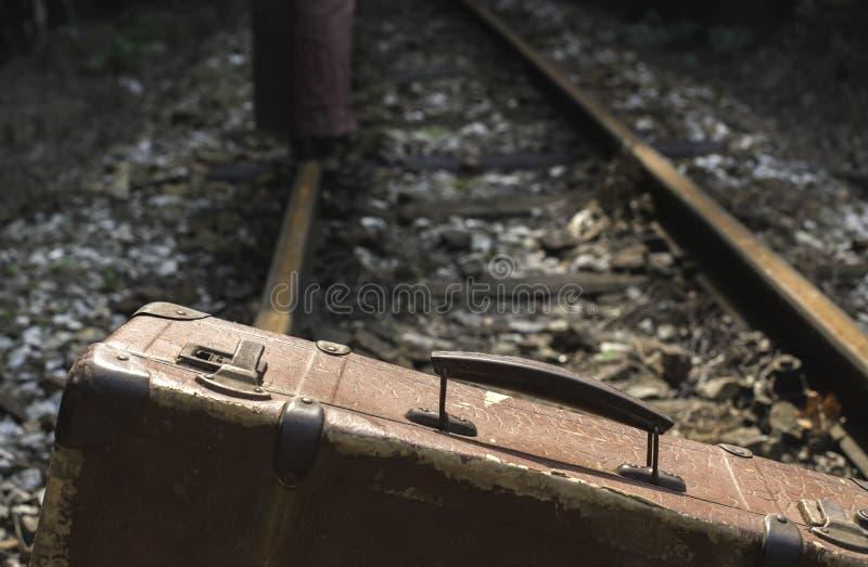 Vrouw en uitstekende koffer op spoorwegweg royalty-vrije stock afbeeldingen