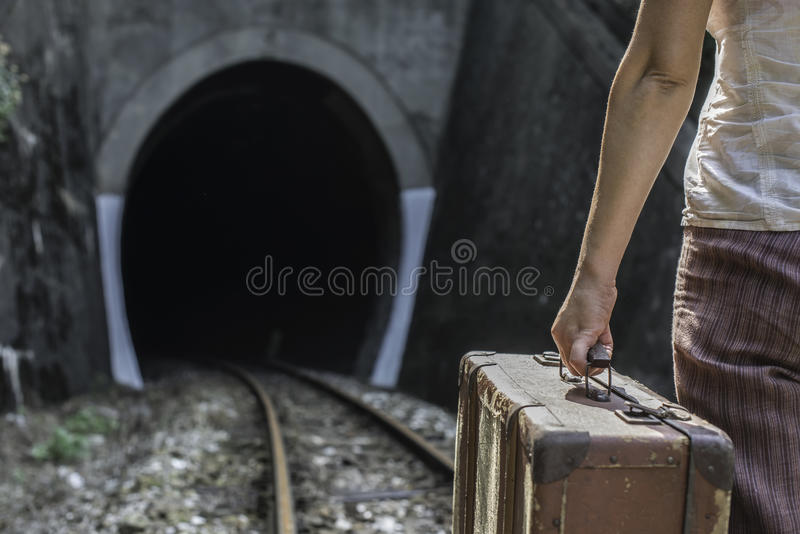 Vrouw en uitstekende koffer op spoorwegweg stock fotografie