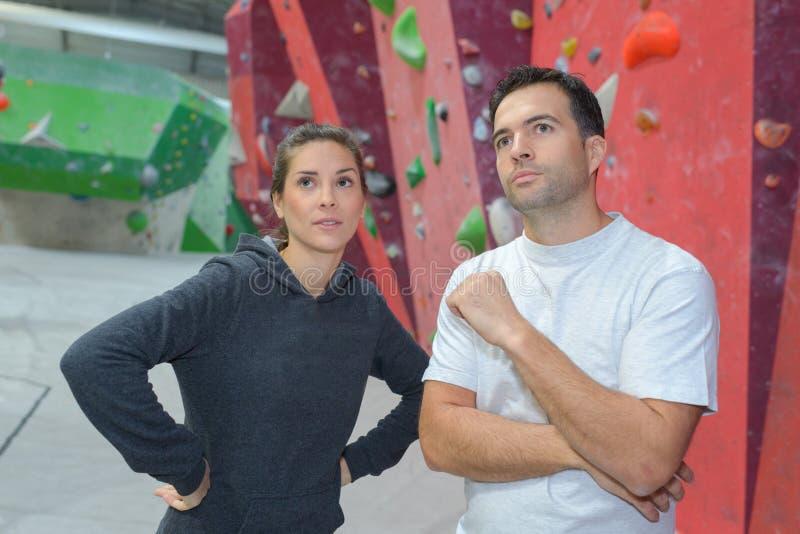 Vrouw en vriend bij bergbeklimmingsmuur bij gymnastiek royalty-vrije stock afbeelding
