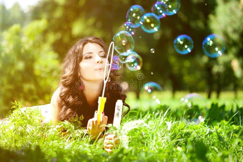 Vrouw en zeepbels in park Mooi jong meisje die op Th liggen stock foto