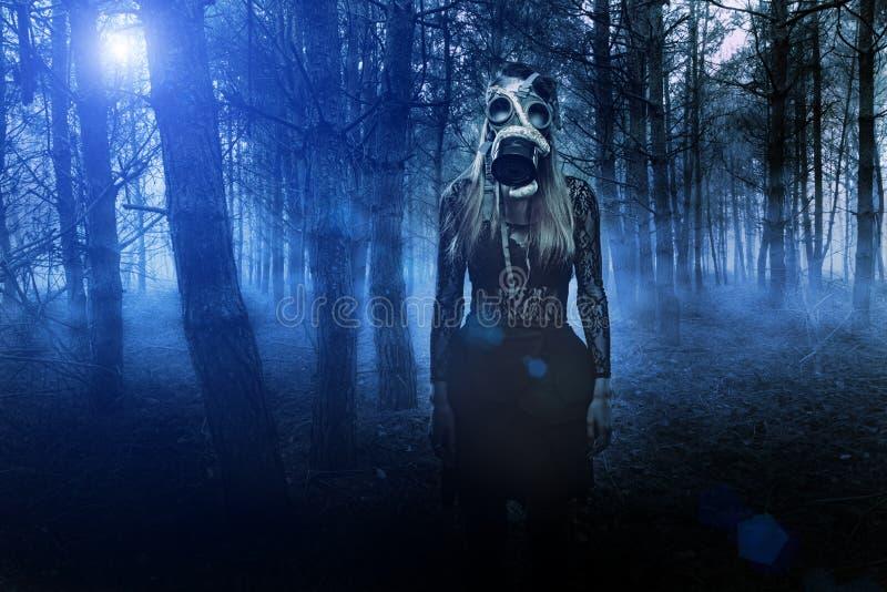 Vrouw in gasmasker met slang in het bos stock fotografie