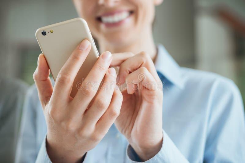 Vrouw gebruikend een smartphone en leunend op een venster stock fotografie