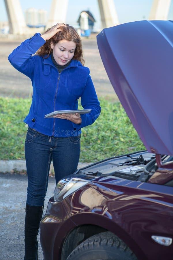 Vrouw in gedachte die zich dichtbij auto met tabletPC bevindt stock afbeelding