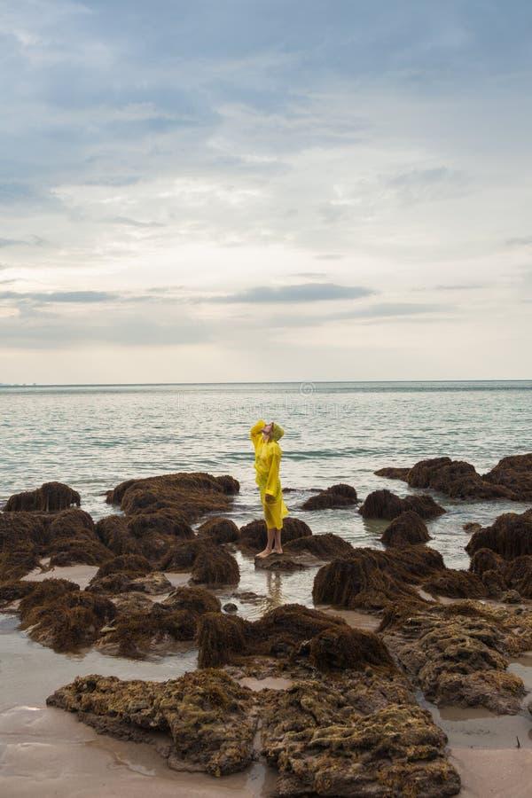 Vrouw in gele regenjas die zich in de oceaan bevinden stock foto's