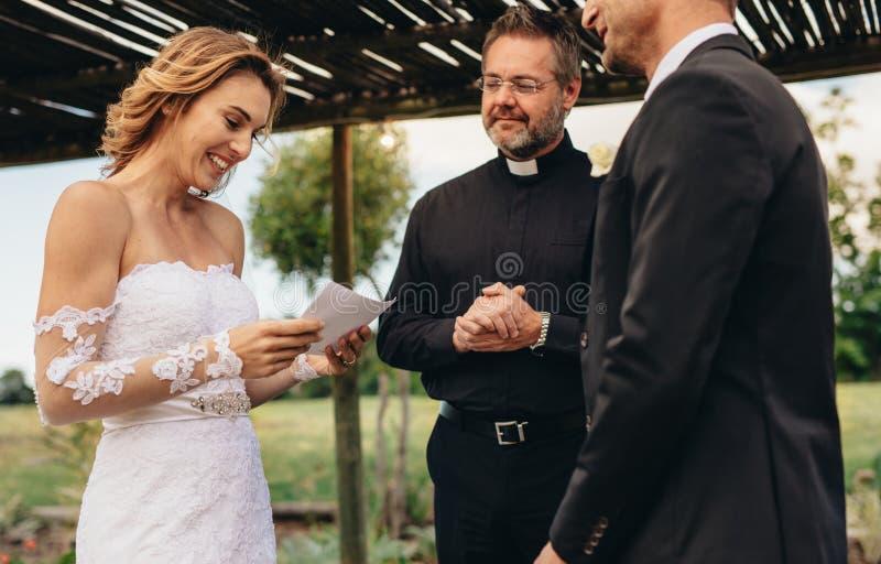 Vrouw gelezen huwelijksgeloften voor haar echtgenoot royalty-vrije stock foto