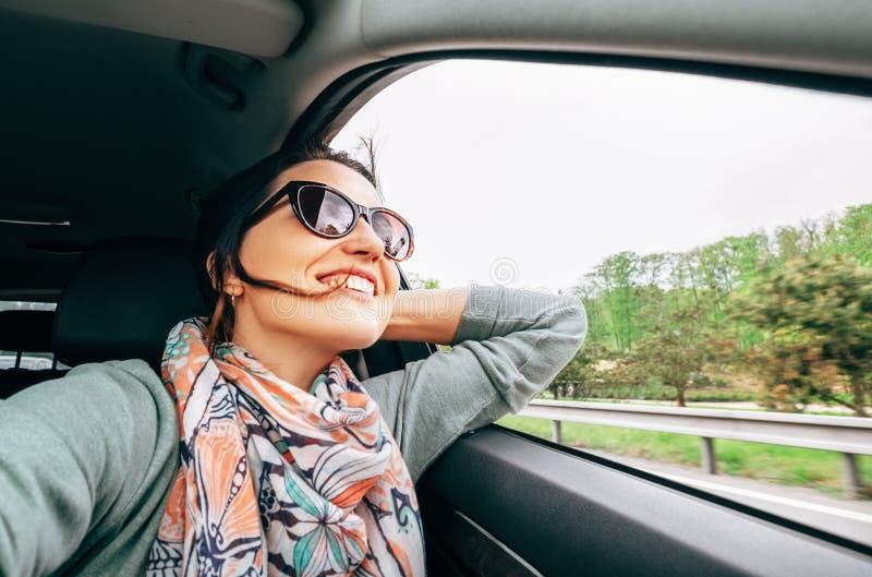 Vrouw geniet van het zicht vanaf het raam van de auto wanneer het reizen met auto royalty-vrije stock afbeelding