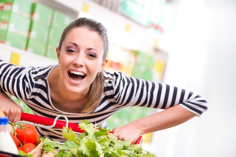 Vrouw genieten die bij supermarkt winkelen royalty-vrije stock foto's