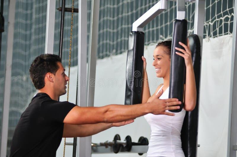 Vrouw in geschiktheidsclub met trainer stock afbeelding