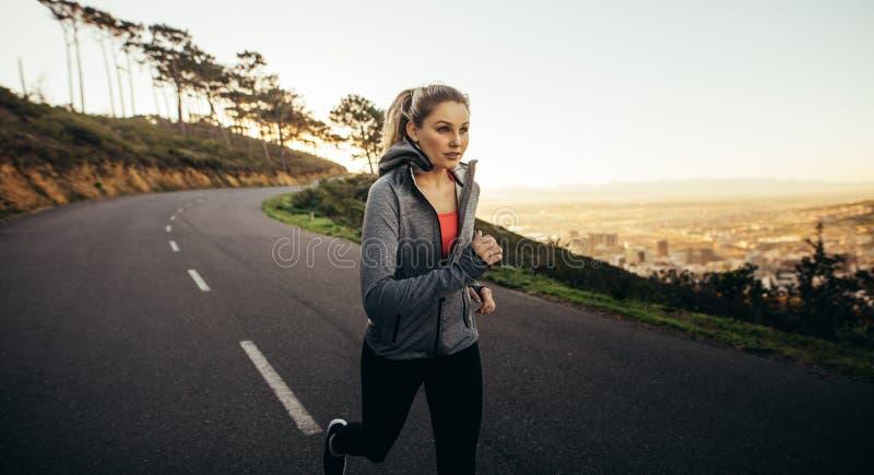 Vrouw in geschiktheidsslijtage die op een lege straat in de ochtend lopen De jogging van de geschiktheidsvrouw op een heuvelige w stock foto