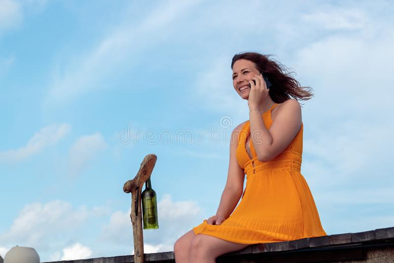 Vrouw gezet op een pijler in een tropische plaats die zijn smartphone en het glimlachen gebruiken Hemel met wolken als achtergron stock foto's