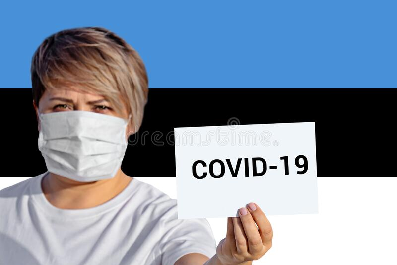 Vrouw in gezichtsmasker greep plaat met opschrift COVID-19 tegen Estse vlag royalty-vrije stock afbeelding